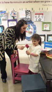 Little girl handing mom a paper rose in our Art Studio
