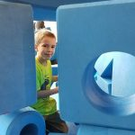 Boy posing between oversized foam construction shapes at Waukegan Pop-Up