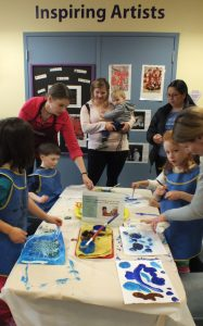 Adults and children working on watercolor paintings together in our Art Studio