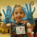 Smiling girl holding up her hands wearing gloves at the Dr for a Day event