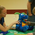 Woman demonstrating how to brush teeth using a stuffed dinosaur toy and oversized toothbrush at the Dr for a Day event