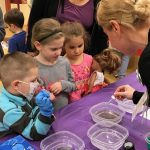 Woman using water and pepper to demonstrate germs to children attending Dr for a Day event