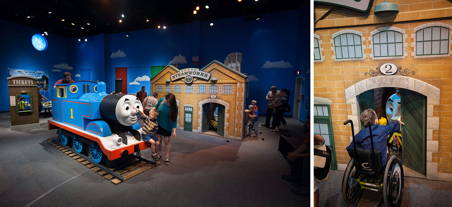 photo of child sitting on Thomas the Tank engine, and child in wheel chair opening the door of the garage to find another character inside.
