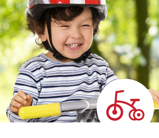 smiling young boy on trike with helmet