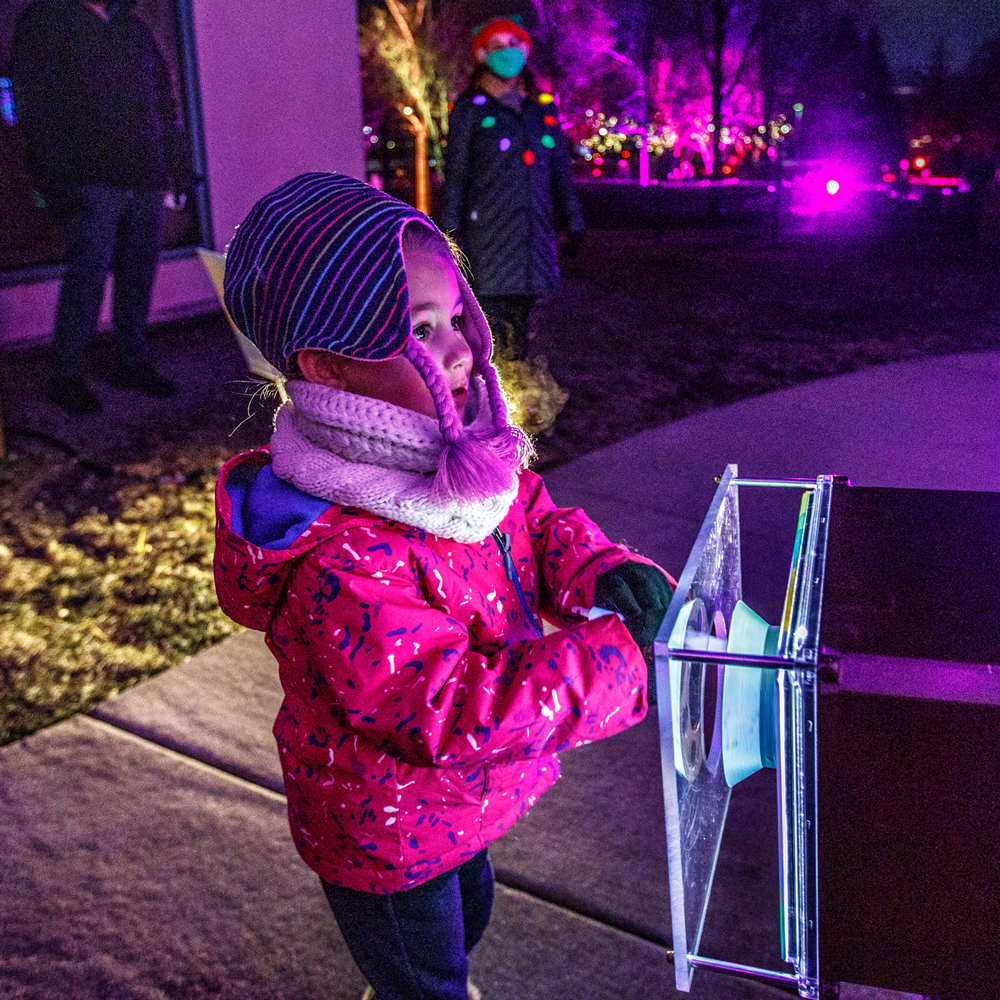 young child interacting with lights
